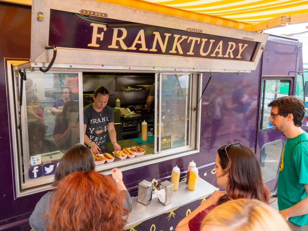 Franktuary Food Truck serving hot dogs at a festival.